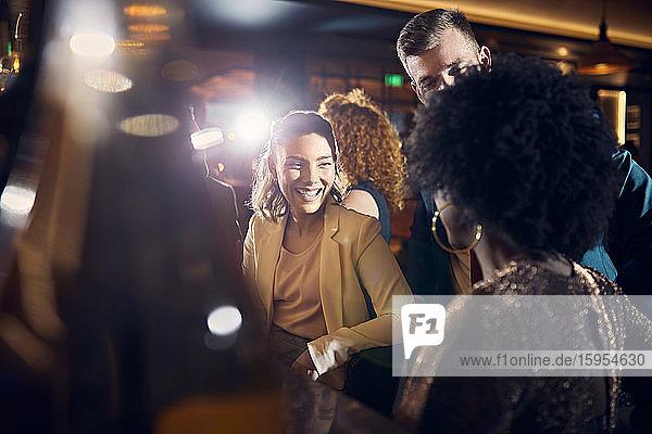 Glückliche Freunde beim geselligen Beisammensein in einer Bar Glückliche Freunde beim geselligen Beisammensein in einer Bar