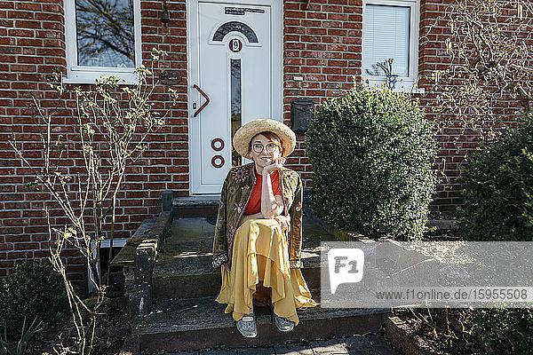 Porträt einer lächelnden reifen Frau mit Strohhut  die auf der Treppe eines Einfamilienhauses sitzt