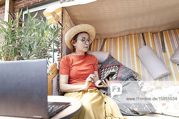 Reife Frau sitzt auf der Terrasse und benutzt ein Smartphone
