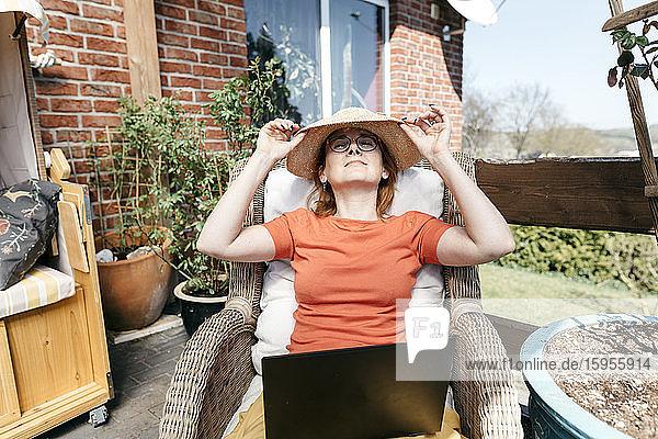 Reife Frau mit Laptop entspannt sich auf der Terrasse