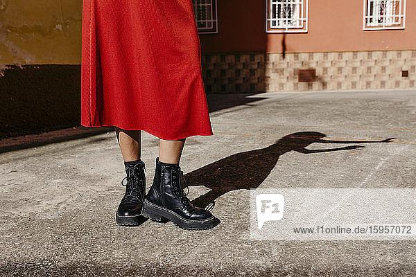Junge Frau in rotem Kleid und schwarzen Stiefeln  die mit ihrem Schatten auf dem Boden spielt