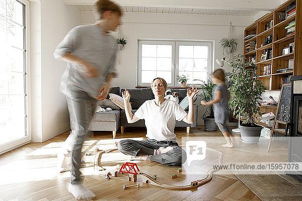 Mutter meditiert inmitten von Spielzeug  Whilchirdren rennen um sie herum