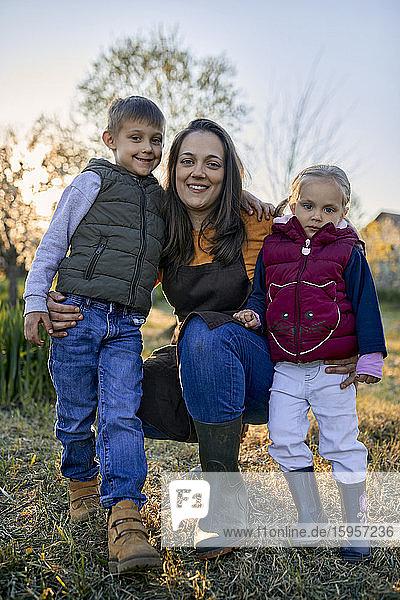 Porträt einer glücklichen Mutter mit zwei Kindern im Garten Porträt einer glücklichen Mutter mit zwei Kindern im Garten