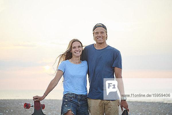 Ein junges Paar  Mann und Frau  skateboarden bei Sonnenuntergang am Strand.