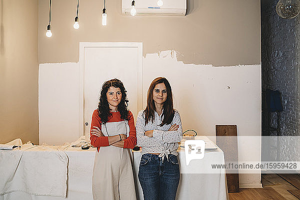 Two mid adult women leaning against table while painting in their new shop  portrait
