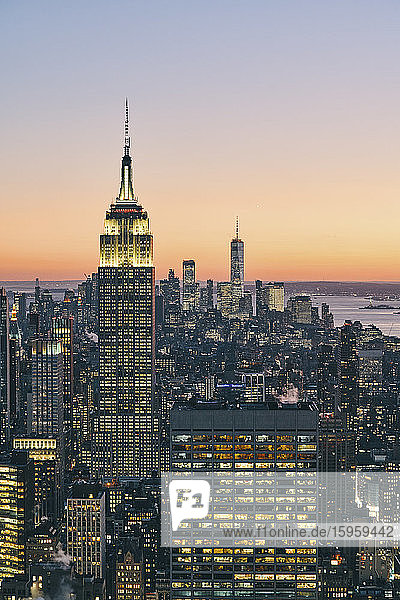 View of Manhattan skyline with illuminated Empire State Building at sunset  New York City