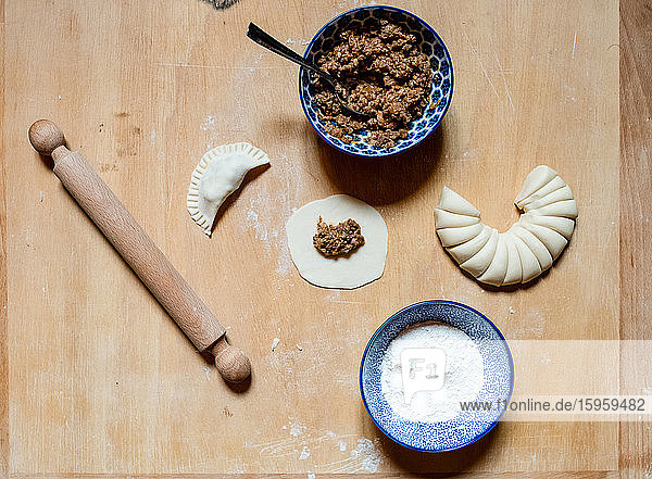 High angle close up of gyoza ingredients and rolling pin on wooden board in a Ramen and Gyoza restaurant in Italy.