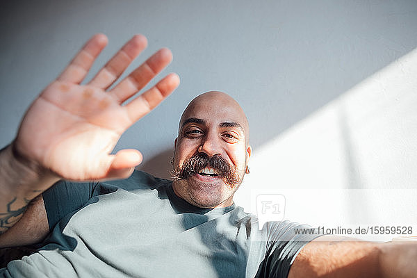 Bald man with moustache self isolating during Corona crisis  smiling and waving at camera.