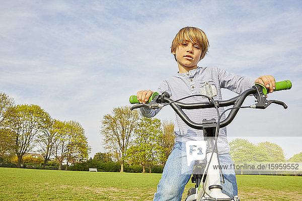 Brunette boy riding his BMX bike in a park.