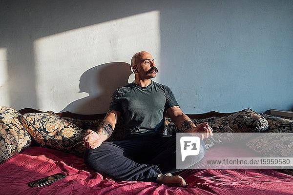 Bald man with moustache sitting on sofa  meditating while self isolating during Corona crisis.
