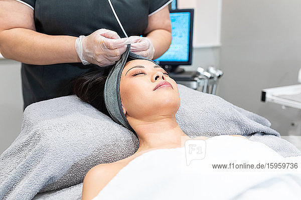 High angle view of woman lying on treatment bed in a beauty salon  receiving facial treatment.