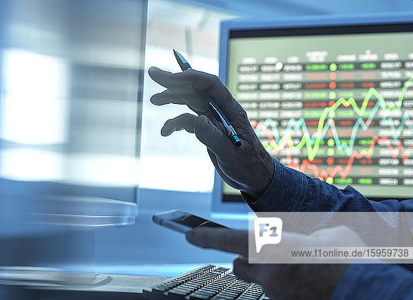 Close up of stock market trader analyzing share price data on the screen.