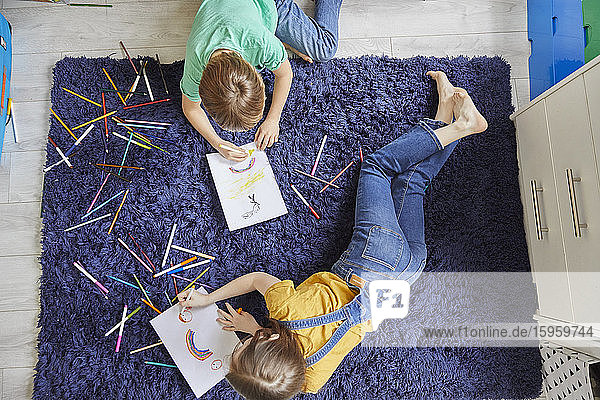 High angle view of boy and girl lying on blue rug  drawing with colouring pencils.
