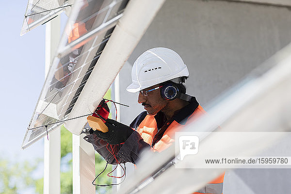 Male engineer wearing hardhat and ear protectors working on construction site.