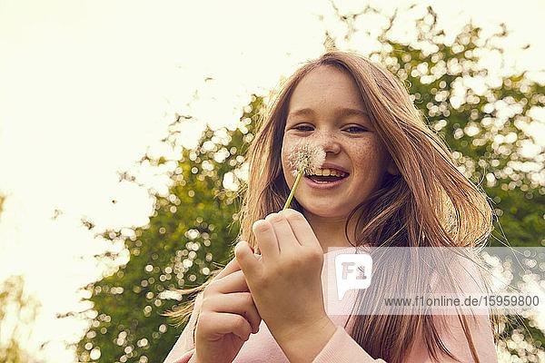 Portrait of smiling girl with long brunette hair standing outdoors  holding dandelion.