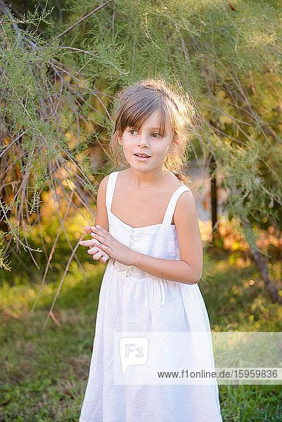 Portrait of girl wearing white summer dress standing in garden.