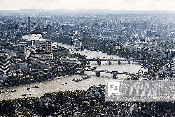 Aerial view of the City of London and the River Thames towards the west  with landmarks like the London Eye  and rooftops.