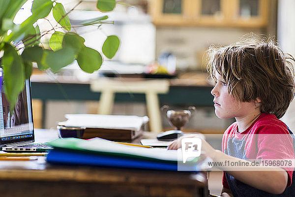 6-jähriger Junge benutzt Laptop für Fernschulung zu Hause