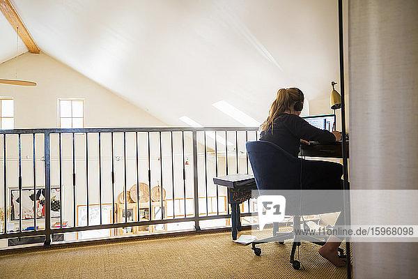 Teenagerin mit Kopfhörern  die zu Hause auf einen Laptop-Computer schaut