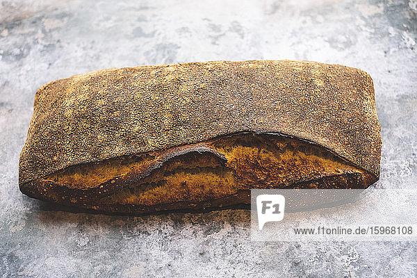 Handwerkliche Bäckerei  die ein spezielles Sauerteigbrot herstellt  einen gebackenen Laib mit fester dunkler Kruste.