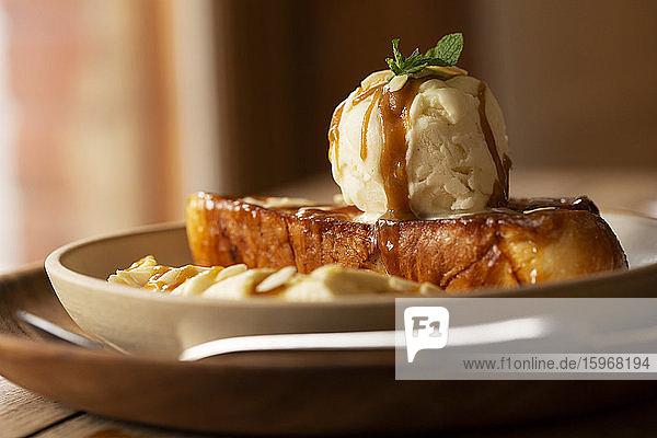 Nahaufnahme von French Toast mit Bananenscheiben und Eis in einem Cafe.