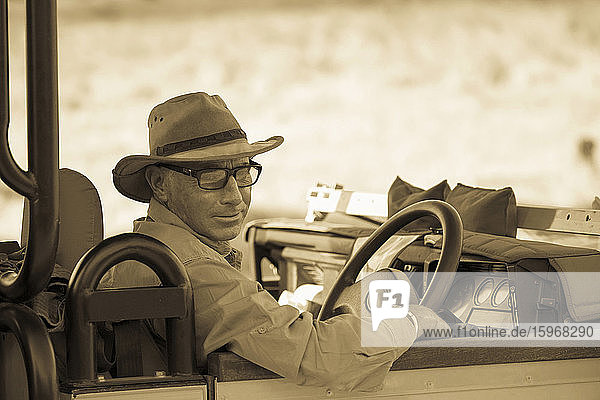 Ein reifer Mann mit Hut und Brille auf dem Fahrersitz eines Jeeps  Sepiaton.