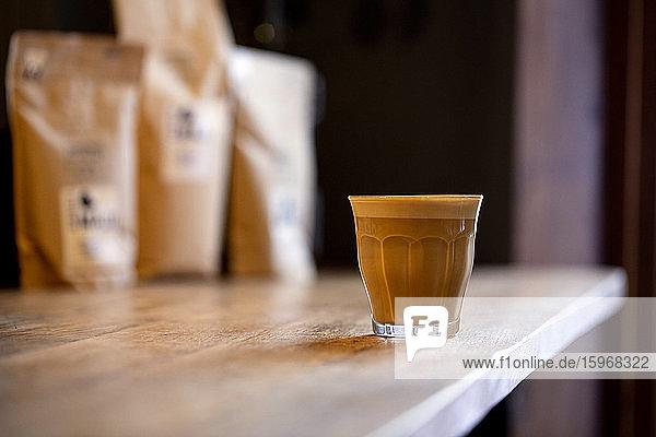 Nahaufnahme eines Glases Cafe Latte auf einem rustikalen Holztisch in einem Café.