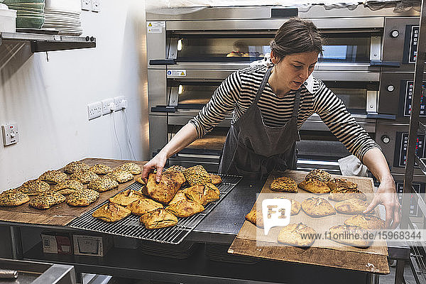 Ein Bäcker  der gebackene  entkernte Brötchen auf ein Blech lädt.