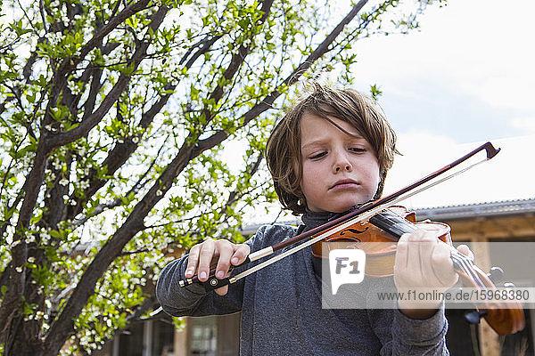 6-jähriger Junge spielt ausserhalb seines Hauses Geige