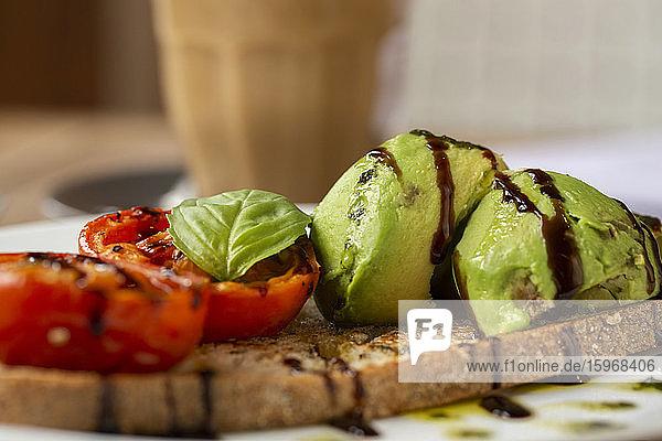 Nahaufnahme von Tomaten- und Avocado-Bruschetta mit Balsamico-Essig-Reduktion in einem Café.