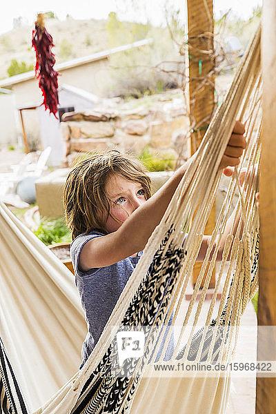 Sechsjähriger Junge schaukelt in einer Hängematte auf einer Terrasse.