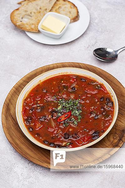 Nahaufnahme einer Tomaten- und Gemüsesuppe mit Beilage von Brot in einem Cafe.