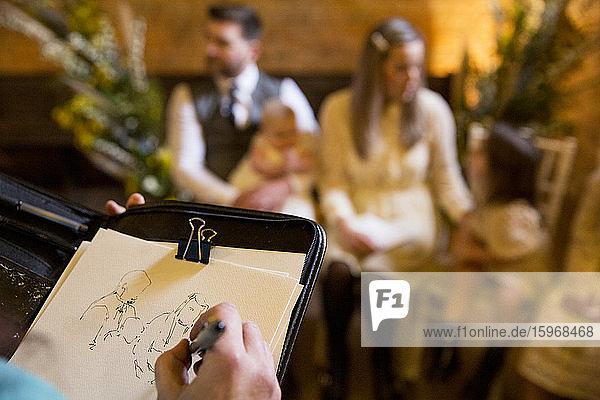 Über-die-Schulter-Ansicht des Künstlers  der die Familie während der Taufzeremonie in einer historischen Scheune skizziert.