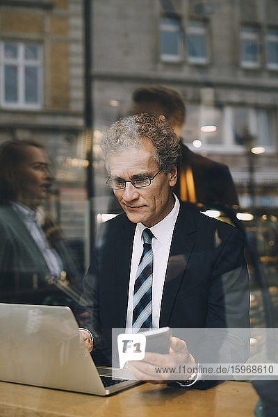 Smiling businessman with smart phone using laptop in cafe seen through glass window