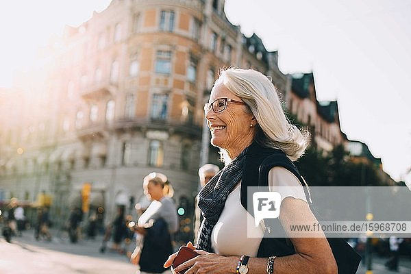Smiling wrinkled woman looking away in city