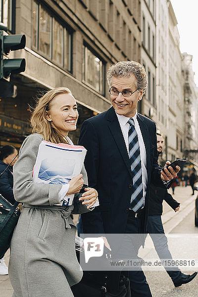 Lächelnde Unternehmerin mit männlichem Kollegen überquert Straße in der Stadt