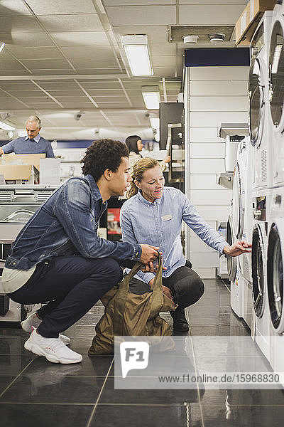 Mature owner explaining about washing machine to male customer in electronics store