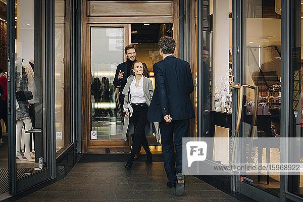 Lächelnde Geschäftsfrau mit männlichem Kollegen in einer Gasse