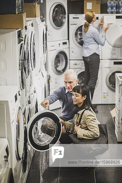 High angle view of mature owner pointing to washing machine while female customer crouching in electronics store