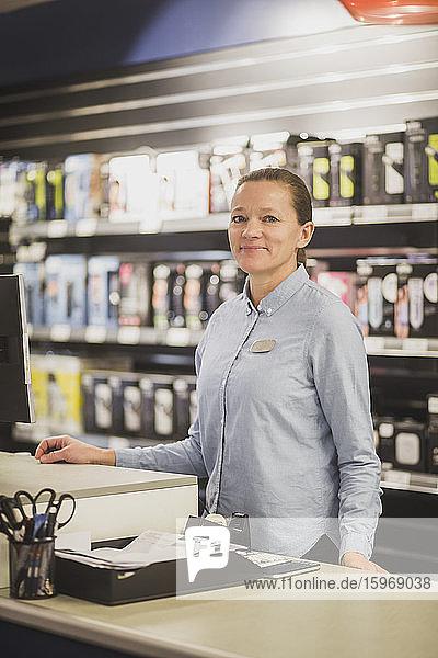 Porträt einer lächelnden reifen Verkäuferin  die in einem Elektronikladen steht