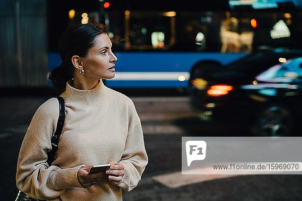 Woman with cellphone looking away while standing in city at night