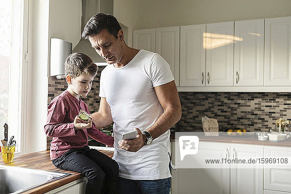 Father showing smart phone to son with food while standing by kitchen counter
