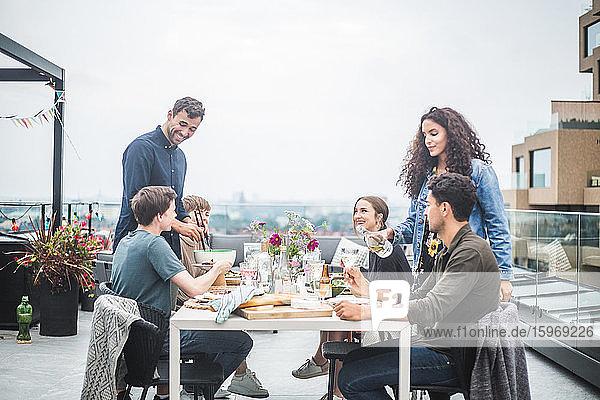 Junger Mann mit Frau serviert Freunden Essen und Getränke während eines geselligen Beisammenseins auf dem Dach