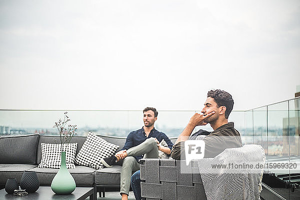 Junge Freunde sitzen auf dem Sofa auf der Gebäudeterrasse