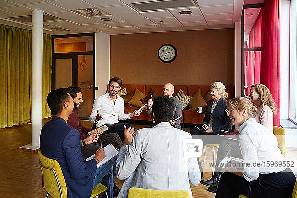Smiling entrepreneurs discussing while sitting in circle during office workshop