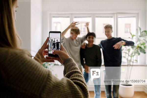Teenagerin mit Handy filmt männliche Freunde beim Tanzen im Wohnzimmer