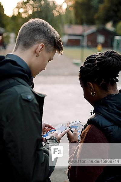 Männliche und weibliche Freunde im Teenageralter nutzen App auf Smartphones  während sie auf der Straße stehen
