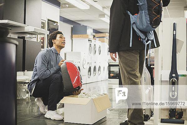 Junger Verkäufer zeigt einem männlichen Kunden im Laden ein Gerät