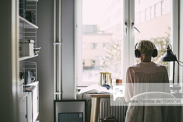Rückansicht einer Frau im Büro zu Hause  die am Schreibtisch sitzt