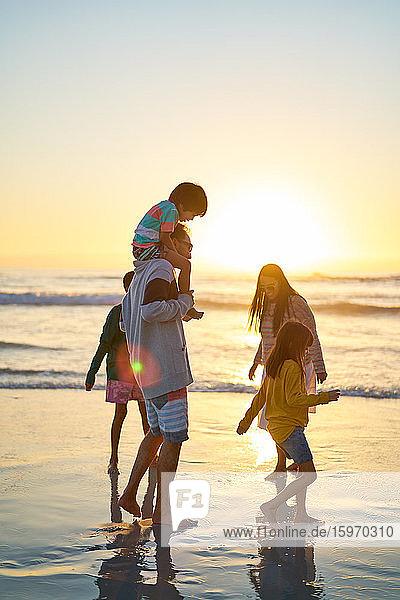 Familie watet bei Sonnenuntergang am sonnigen Strand in der Brandung